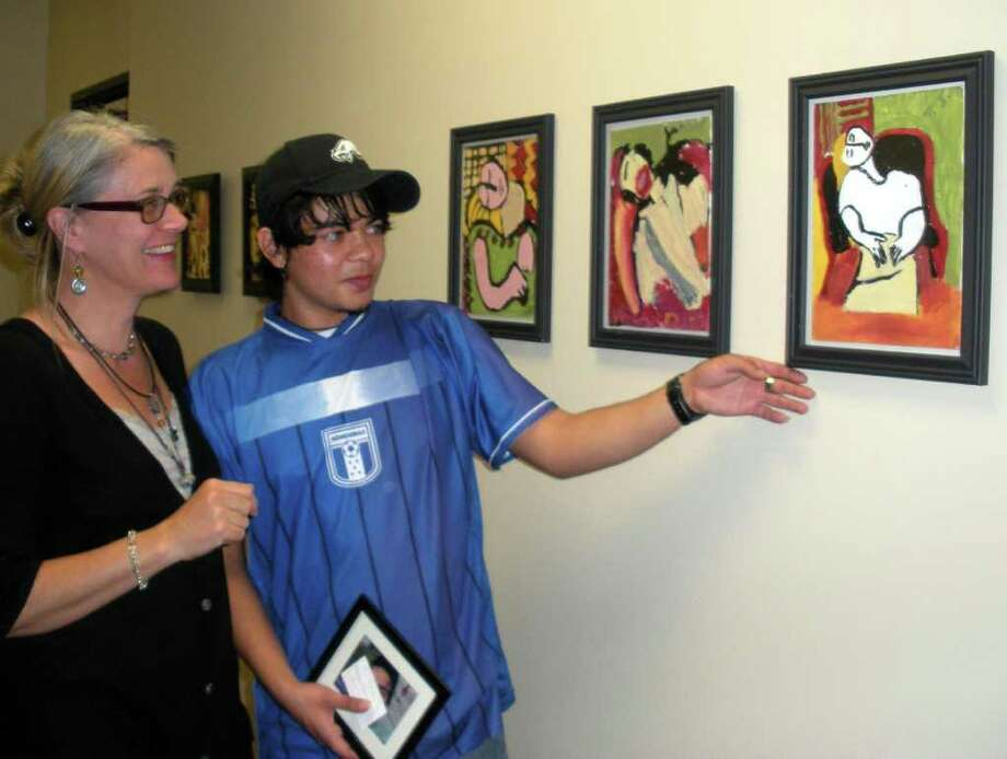 """B.J. POLLOCK PHOTOS: FOR THE CHRONICLE THE WAY I SEE IT: Terri Bieber, founder of ARTreach, and Flavio Jiminez look at his version of Picasso's """"The Dream."""""""