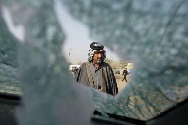 A man is seen through smashed windscreen of a damaged vehicle, inspect the scene of a car bomb attack at a predominantly Sunni area in western Baghdad on Tuesday. Three car bombs exploded Monday evening in the Iraqi capital, killing and wounding scores of people, police said. (AP Photo/Hadi Mizban) Photo: Hadi Mizban, ASSOCIATED PRESS / AP2012