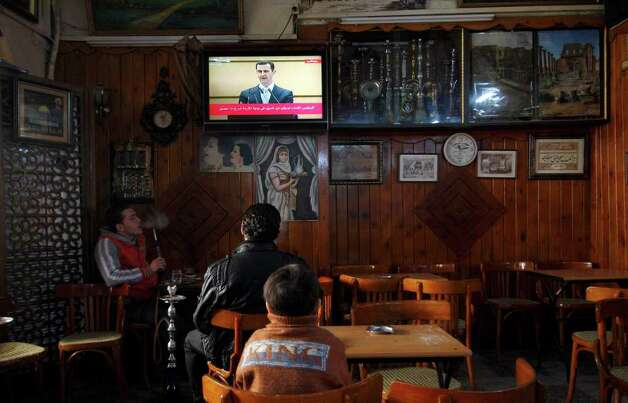 "Syrians watch a televised broadcast of Syrian President Bashar Assad deliver a speech at Damascus University, at a coffee shop in Damascus, Syria, on Tuesday. Assad vowed Tuesday to respond to threats against him with an ""iron hand"" and refused to step down, insisting he still has his people's support despite the 10-month-old uprising against him. (AP Photo/Muzaffar Salman) Photo: Muzaffar Salman, ASSOCIATED PRESS / AP2012"