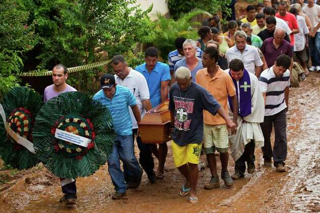 Relatives carry the coffins of a family that was killed by a mudslide to the cemetery in Jamapara, Rio de Janeiro state, Brazil, Tuesday. Sergio Carvalho, his wife, Solange, and their son, Tiago, were buried by a mudslide. Civil defense officials say the mudslide caused by two days of downpours has killed at least 13 people in Rio de Janeiro state, while in neighboring Minas Gerais state at least 15 have died. Photo: AP
