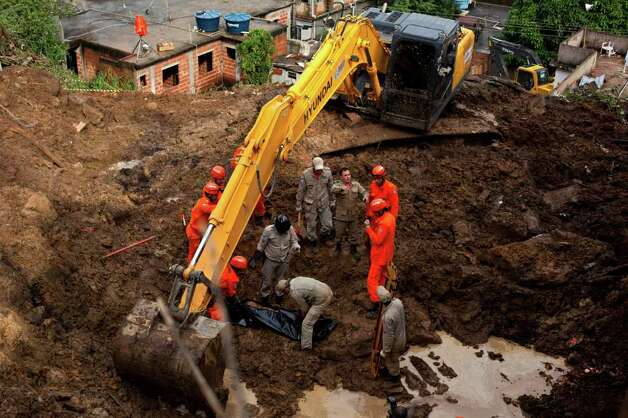Rescue personnel recover the body of a mudslide victim in Jamapara, Rio de Janeiro state, Brazil, on Tuesday.  Heavy rains caused mudslides that killed at least eight people in Rio de Janeiro state Monday, raising the number of dead in Rio and neighboring Minas Gerais state to 23 so far this year, and up to 20 other people are still missing, according to civil defense officials. Photo: AP