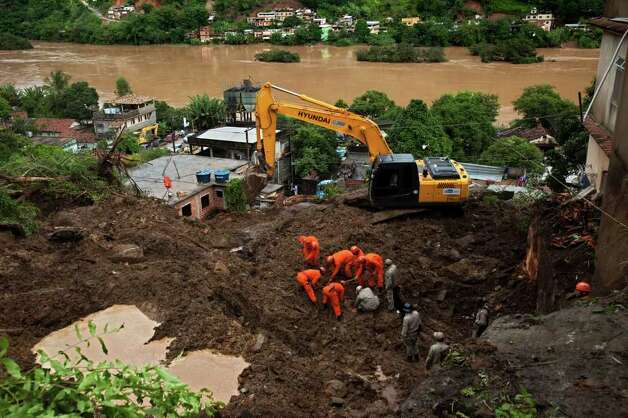 Rescue workers recover the body of a mudslide victim in Jamapara, Rio de Janeiro state, Brazil, on Tuesday. Heavy rains caused mudslides that killed at least eight people in Rio de Janeiro state Monday, raising the number of dead in Rio and neighboring Minas Gerais state to 23 so far this year, and up to 20 other people are still missing, according to civil defense officials. Photo: AP