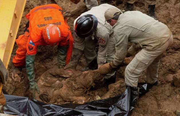 Rescue personnel recover the body of a mudslide victim in Jamapara, Rio de Janeiro state, Brazil, on Tuesday.  Civil defense officials say the mudslide caused by two days of downpours has killed at least 13 people in Rio de Janeiro state, while in neighboring Minas Gerais state at least 15 have died. Photo: AP