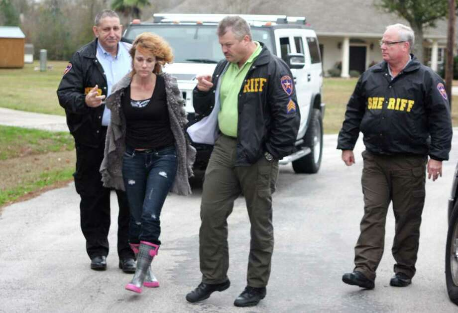 Warrant Round-up in Hardin County. Deputies place Heather Victoria Thibodeaux under arrest and lead her to a waiting patrol vehicle after she was served a warrant for possession of drug paraphernalia. Photo: David Lisenby, HCN_Roundup