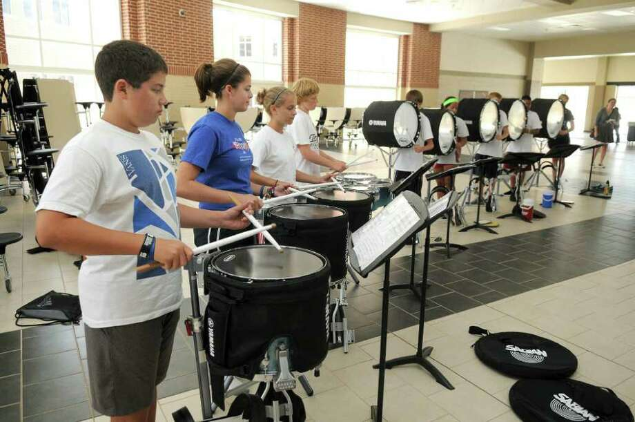 JERRY BAKER: FOR THE CHRONICLE DRUMLINE TIME: Nathan Edwards, 15, from left, a sophomore, Sienna Hopkins, 15, a sophomore, Sophie Pearsen, 14, a freshman, Patrick Trotter, 14, a freshman, and the rest of the Tomball Memorial High School Band drumline practice in the school cafeteria. Photo: Jerry Baker