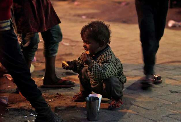 A homeless child eats biscuits with tea on a street in New Delhi, India, on Tuesday. A new study says 42 percent of children in India under the age of five are underweight and nearly 60 percent are stunted. The Hunger and Malnutrition Survey was released Tuesday, Jan. 10, 2012, and surveyed over 100,000 children in 112 districts across nine states in the country. These included 100 districts with the worst child development indicators. Photo: Mustafa Quraishi, AP / AP