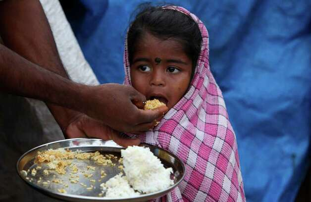 An Indian child is fed by her father at a shanty area in Hyderabad, India, on Tuesday. A new study says 42 percent of children in India under the age of five are underweight and nearly 60 percent are stunted. The Hunger and Malnutrition Survey was released Tuesday and surveyed over 100,000 children in 112 districts across nine states in the country. These included 100 districts with the worst child development indicators. Photo: AP