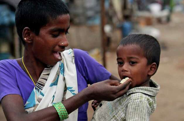 An Indian woman feeds her child at a shanty area in Hyderabad, India, on Tuesday. A new study says 42 percent of children in India under the age of five are underweight and nearly 60 percent are stunted. The Hunger and Malnutrition Survey was released Tuesday and surveyed over 100,000 children in 112 districts across nine states in the country. These included 100 districts with the worst child development indicators. Photo: AP