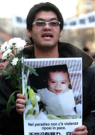 "A man holds a picture of the baby who was killed during a robbery and reading ""There is no violence in paradise, rest in peace "", during a march to honor a Chinese father and his baby shot dead by thieves, in Rome Tuesday. People gathered days after robbers shot and killed a man and his 8-month-old child outside their home in Rome. Police say the killings occured Wednesday when robbers confronted a Chinese immigrant, his wife and daughter, and demanded receipts from the family's business. Photo: Pier Paolo Cito, AP / AP"