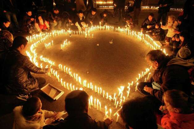 Residents light candles during a vigil to honor a Chinese father and his baby shot dead by thieves, in Rome.  Photo: Roberto Monaldo, AP / PRESL