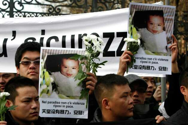 "People hold up pictures of a old baby who was killed during a robbery and reading ""There is no violence in paradise, rest in peace "", during a march to honor a Chinese father and his baby shot dead by thieves, in Rome, Tuesday, Jan. 10, 2012. People gathered days after robbers killed a man and his 8-month-old child outside their home in Rome. Police say the killings occured Wednesday when robbers confronted a Chinese immigrant, his wife and daughter, and demanded receipts from the family's business. Photo: Pier Paolo Cito, AP / AP"
