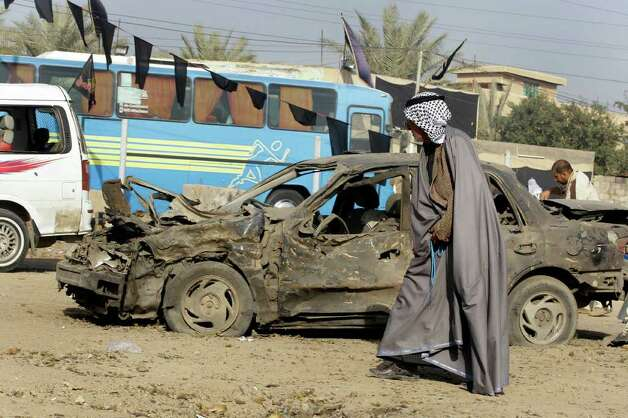 People inspect the scene of a car bomb attack at a predominantly Sunni area in western Baghdad on Tuesday. Three car bombs exploded Monday evening in the Iraqi capital, killing and wounding scores of people, police said. (AP Photo/Hadi Mizban) Photo: Hadi Mizban, ASSOCIATED PRESS / AP2012