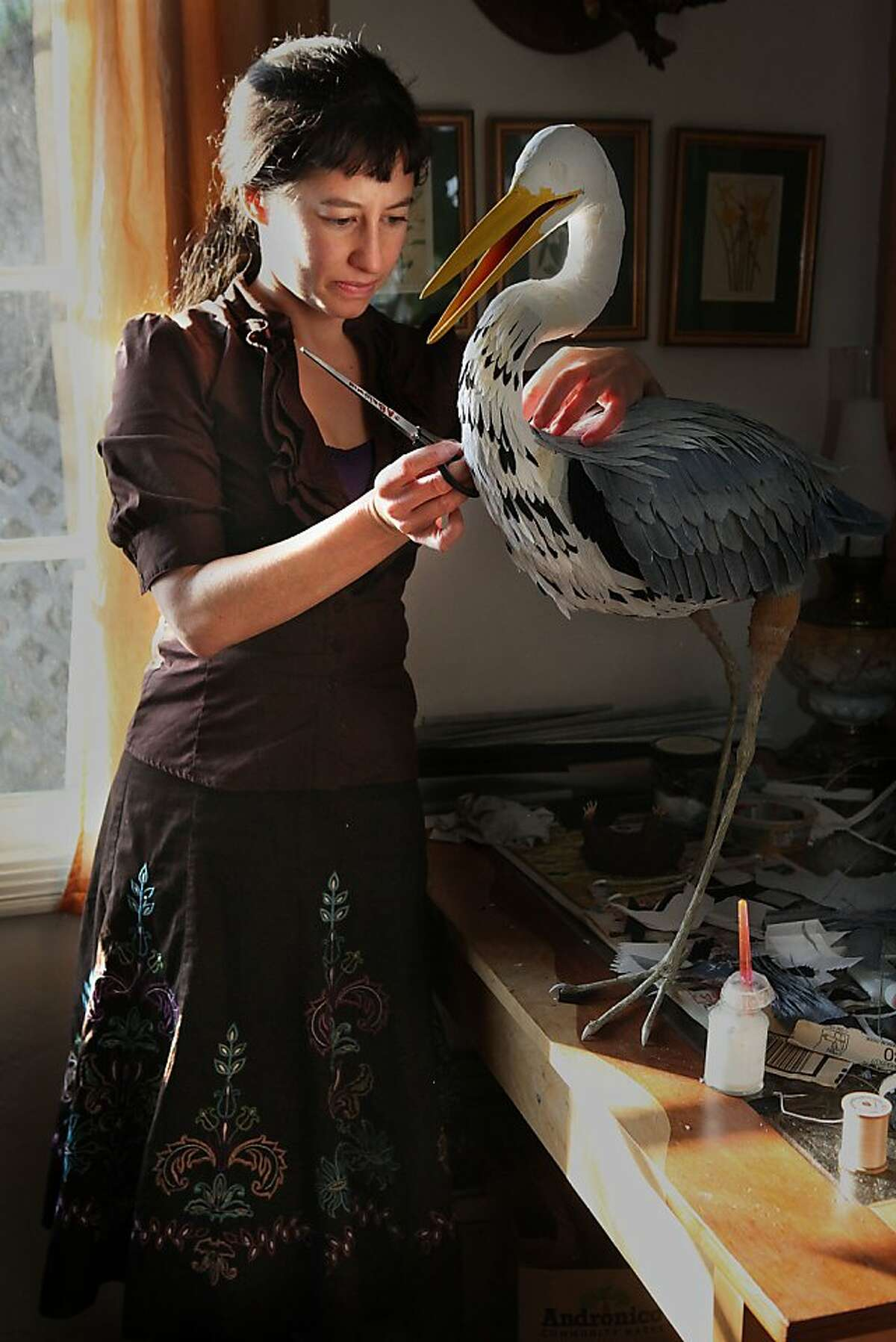 Aimee Baldwin working on a blue heron as she makes its feathers out of crepe paper in Berkeley, Calif., on Tuesday, December 13, 2011.