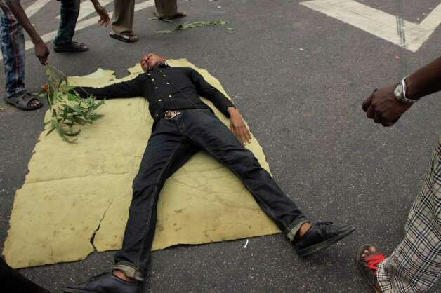 A protester lays on the main road on the second day of the ongoing strike following the removal of  fuel subsidy by the government in Lagos, Nigeria, on Tuesday. As Nigeria's nationwide strike starts its second day, angry youths have erected a burning roadblock outside luxury enclaves in Lagos the commercial capital of the west African nation. Photo: Sunday Alamba, AP / AP