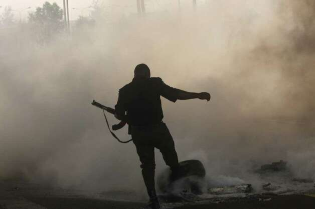 A police officer tries to extinguish a burning roadblock following a protest over the removal of a fuel subsidy by the government in Lagos, Nigeria, on Tuesday. Angry youths erected a burning roadblock outside luxury enclaves in Nigeria's commercial capital Tuesday as a paralyzing national strike over fuel prices and government corruption entered its second day.(AP Photo/Sunday Alamba) Photo: Sunday Alamba, ASSOCIATED PRESS / AP2012