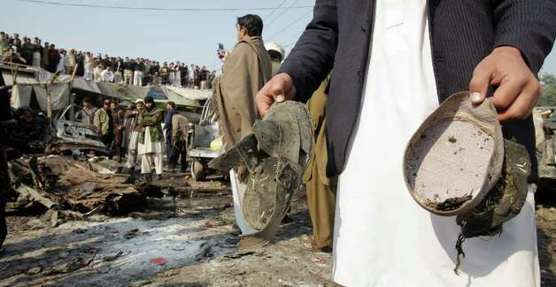 A man shows cap and shoe of victims at the site of an explosion in Pakistani tribal area of Khyber near Peshawar, Pakistan on Tuesday. A bomb targeting a militia opposed to the Pakistani Taliban exploded in a market close to the Afghan border Tuesday, killing many people in the deadliest blast in the country in several months, officials said. (AP Photo/Mohammad Sajjad) Photo: Mohammad Sajjad, ASSOCIATED PRESS / AP2012