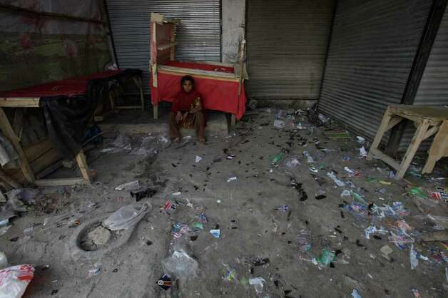 A Pakistani girl sits outside closed shops after an explosion in Pakistani tribal area of Khyber near Peshawar, Pakistan on Tuesday A bomb targeting a militia opposed to the Pakistani Taliban exploded in a market close to the Afghan border Tuesday, killing many people in the deadliest blast in the country in several months, officials said. (AP Photo/Mohammad Sajjad) Photo: Mohammad Sajjad, ASSOCIATED PRESS / AP2012