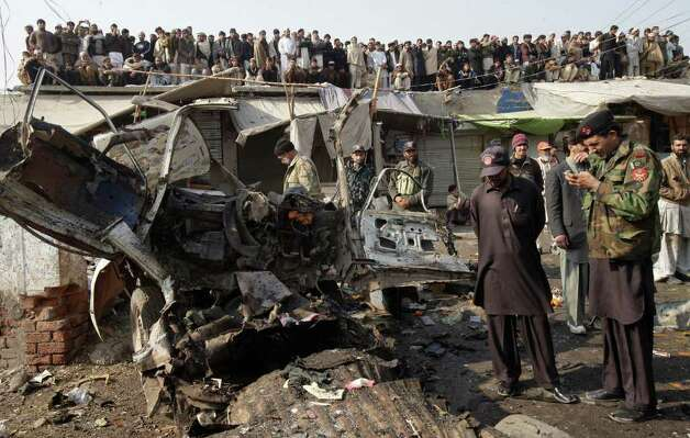 Pakistani security personnel inspect the site of explosion in Pakistani tribal area of Khyber near Peshawar, Pakistan on Tuesday. A bomb targeting a militia opposed to the Pakistani Taliban exploded in a market close to the Afghan border Tuesday, killing 25 people in the deadliest blast in the country in several months, officials said. (AP Photo/Mohammad Sajjad) Photo: Mohammad Sajjad, ASSOCIATED PRESS / AP2012