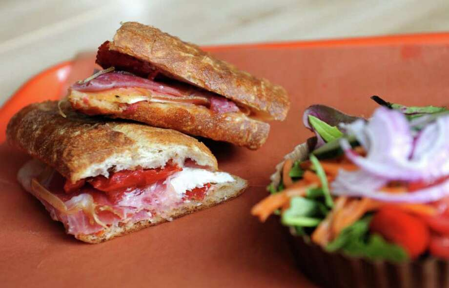 Italian Mozzarella and Prosciutto melt with roasted tomatoes and olive oil on a baguette at Melt Market and Cafe in downtown Bridgeport, Conn.  The new eatery offers artisan cheeses, cured meats, salads, and sandwiches along with specialty grocery items and more. Photo: Autumn Driscoll / Connecticut Post