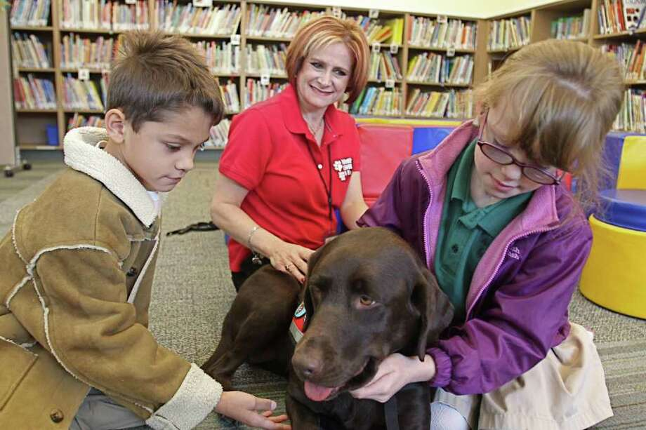 SUZANNE REHAK: FOR THE CHRONICLE SPECIAL VISIT: Pupils at The Parish School, Camden Castorena, 7, left, and Alexandra Eason, 9, pet Godiva, a therapy dog owned by Carey Handley in the back. The school is at 11001 Hammerly Blvd. Photo: Suzanne Rehak