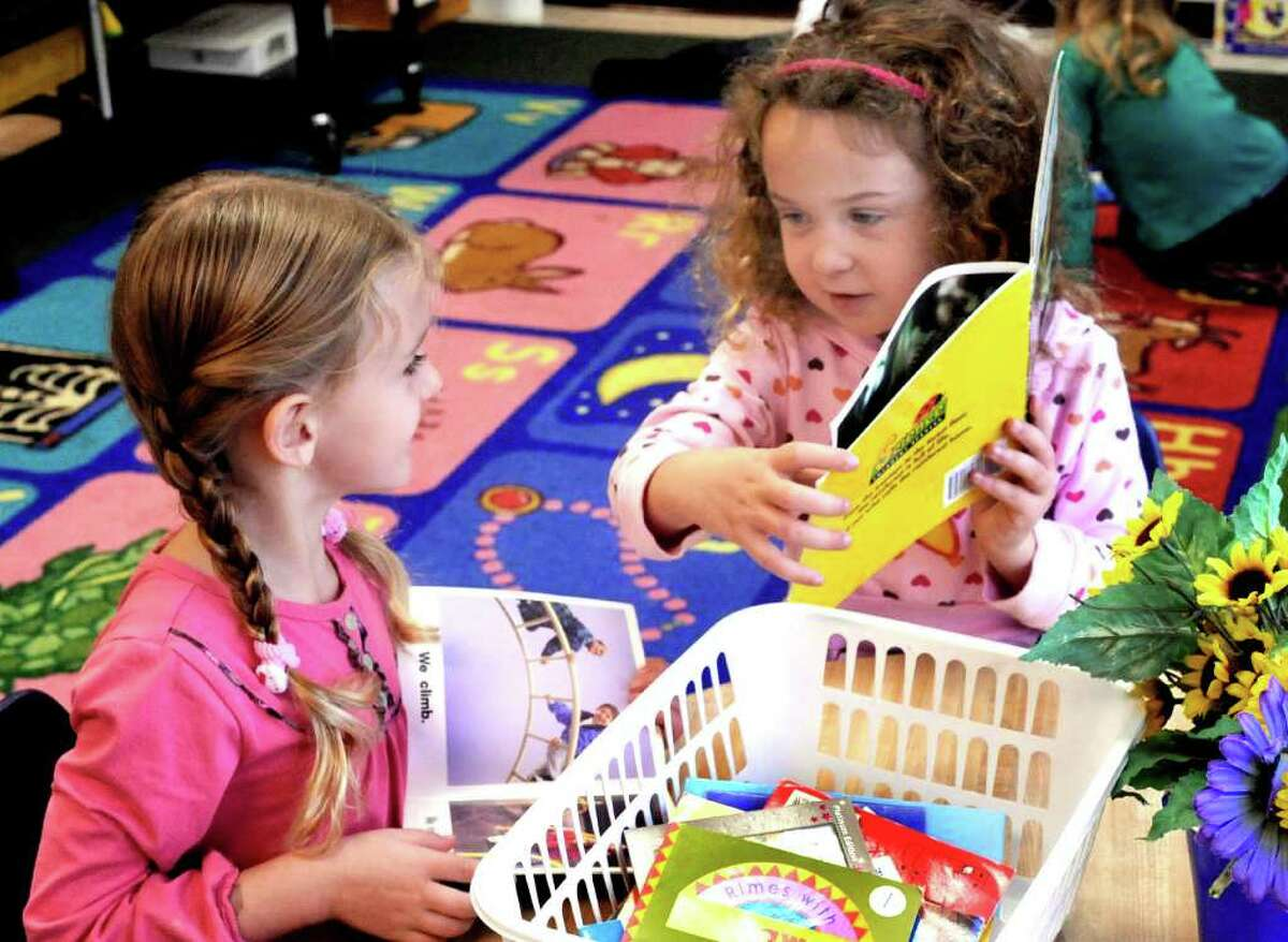 Lilly Morton, left, reads with Arynna DeBenedetto recently in a kindergarten class at the Frank A. Berry School in Bethel.