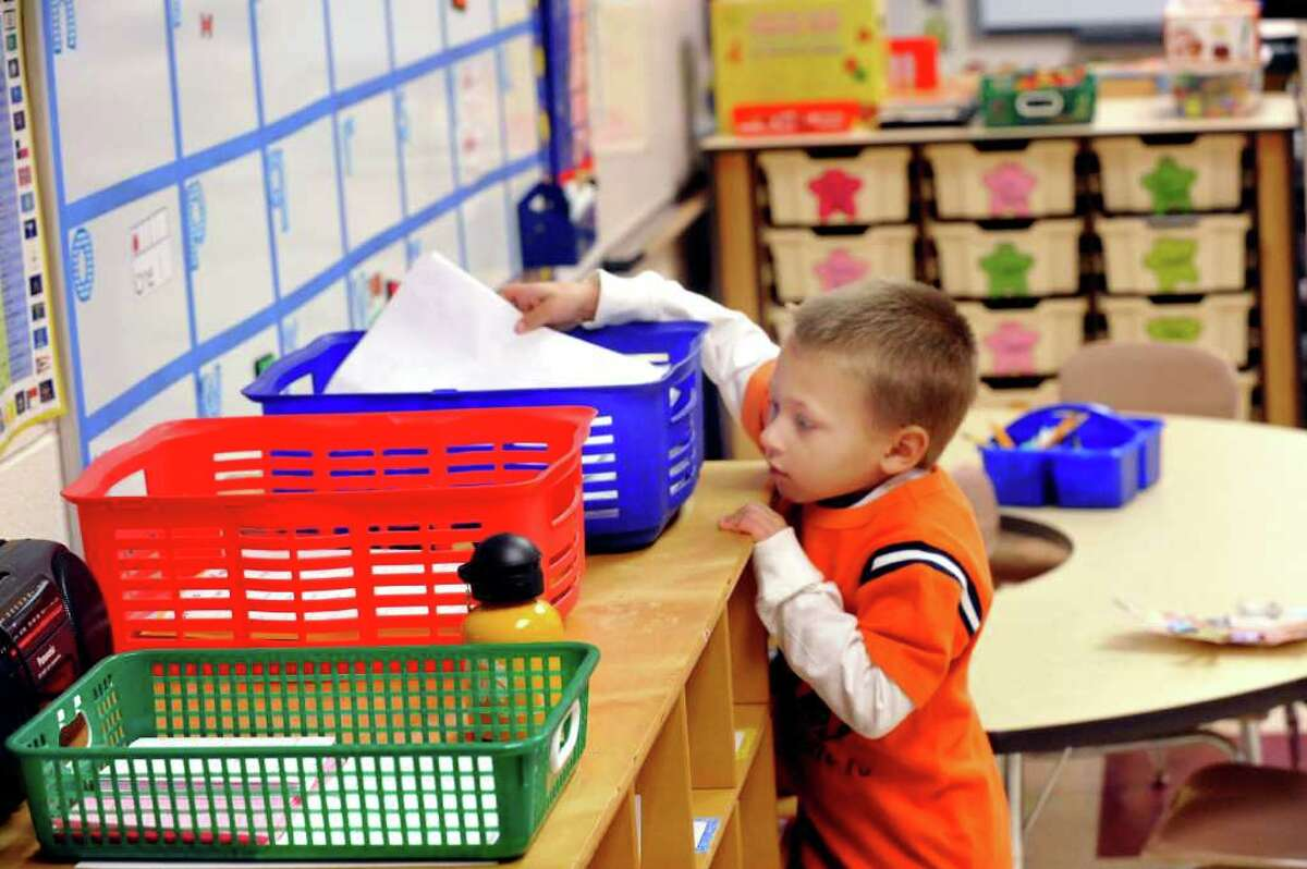 Tommy Prisco submits his homework recently in Mrs. Trombetto's kindergarten class at the Frank A. Berry School in Bethel.