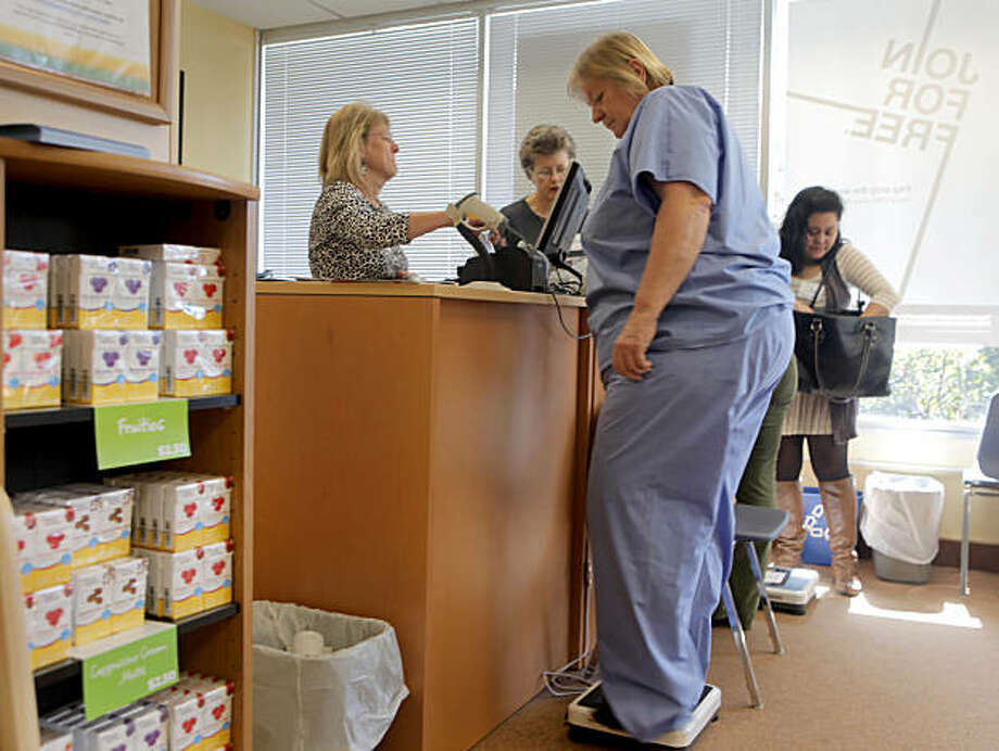 Weight Watchers receptionist Amy Miller, left , records Patty Bauer's weight loss, as Barbara Miller, rea, welcomes a new member, Thursday March 3, 2011, in San Francisco, Calif. Before each meeting the members weigh themselves and report their results.  People who are looking to lose weight  are now counting points which are based on a food's nutritional value instead of just the calories, this has been something that Weight Watchers has done for years. Photo: Lacy Atkins, The Chronicle