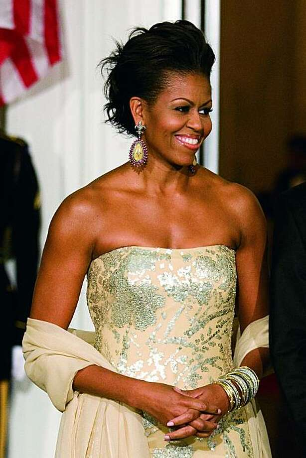 Michelle Obama wears an ivory and silver dress by designer Naeem Khan to the White House's first state dinner in 2009. Photo: Brooks Kraft/Corbis, Courtesy Crown Publishing