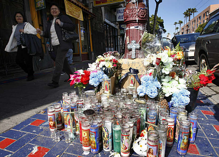 Women walk past a memorial shrine in the Mission District in San Francisco, Calif., on Thursday, March 3, 2011, at the scene of a fatal shooting last weekend. Photo: Paul Chinn, The Chronicle