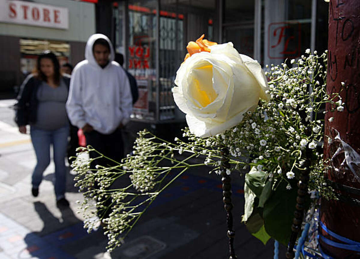 Pedestrians walk past a memorial shrine in the Mission District in San Francisco, Calif., on Thursday, March 3, 2011, at the scene of a fatal shooting last weekend in the Mission District in San Francisco, Calif., on Thursday, March 3, 2011.