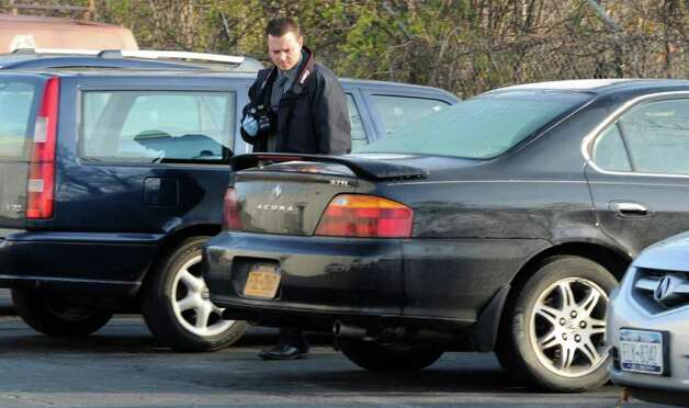 A Colonie Police forensics investigator looks over a car that was subsequently towed on Oct. 31, 2011, from Gold's Gym in Latham, N.Y., after a man died following a struggle with Colonie Police at the gym.     (Skip Dickstein / Times Union archive) Photo: SKIP DICKSTEIN / NWest PRS 2011