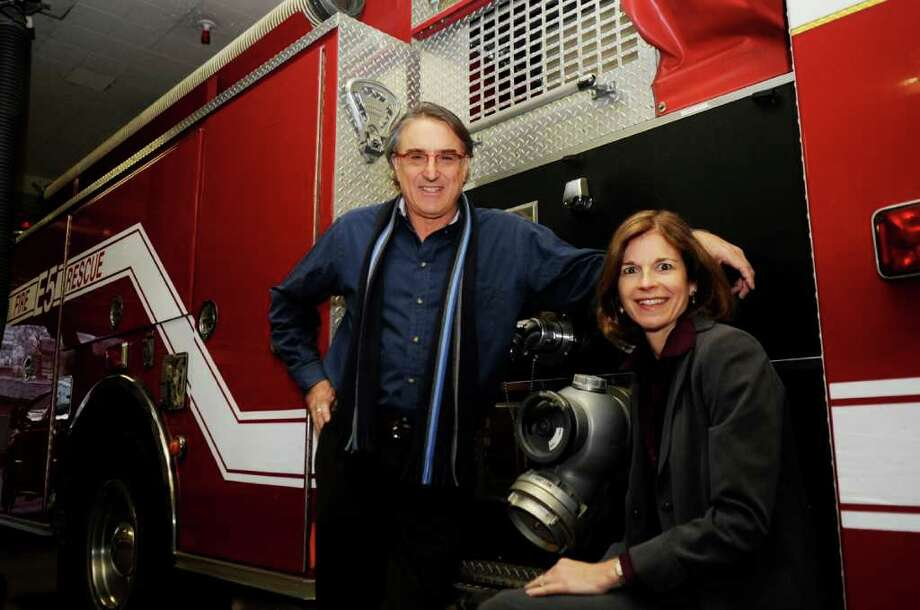 Peter Lobel, a native Zimbabwe, and his wife, Diane, pose at a fire truck at the Sound Beach Volunteer fire Department. The Lobels recently donated two fire trucks to the city of Harare in Zimbabwe. Photo: Helen Neafsey / Greenwich Time