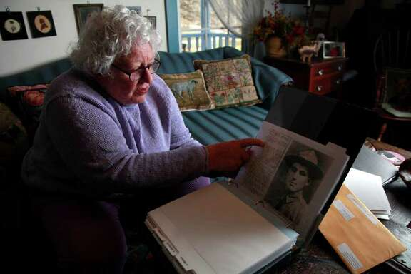 Elsie Shemin-Roth flips through a book documenting the heroic acts of her father, William Shemin, during World War I, last week at her home in Missouri.