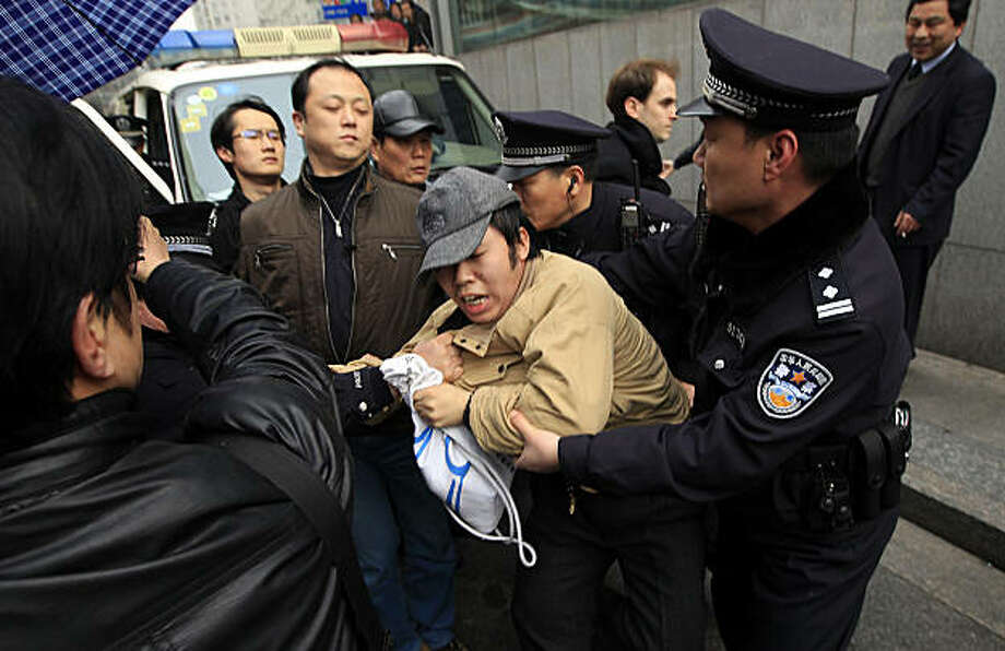 A man, center, is detained by police officers near the planned protest site is located at in Shanghai, China, Sunday, Feb. 27, 2011. Large numbers of police, and use of new tactics like shrill whistles and street cleaners, are squelching any overt protests in China after calls for more peaceful gatherings modeled on recent popular democratic movements in the Middle East. Photo: Eugene Hoshiko, AP