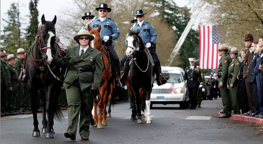 A rideless horse led by a ranger leads a procession to a memorial service for Mount Rainier National Park Ranger Margaret Anderson Tuesday, Jan. 10, 2012, in Tacoma, Wash. Anderson, a 34-year-old mother of two young girls, was shot and killed after setting up a roadblock to stop a vehicle that blew through a checkpoint on the road to the park's visitor center. The driver of that vehicle shot Anderson in her car and ran away. The body of the suspect, 24-year-old Iraq war veteran Benjamin Colton Barnes, was found in a snowy creek the next day, where he died of hypothermia and drowning. Photo: Elaine Thompson / AP