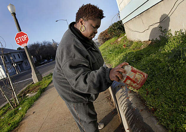 Oshonna Wallace pours grease on the cement retaining wall around her friends home on Marin Street to combat prostitutes from sitting on the wall. The citizens of Vallejo, Calif., have formed watch groups to combat an increase in prostitution in their neighborhoods since the city declared bankruptcy and the police force was cut. Photo: Brant Ward, The Chronicle