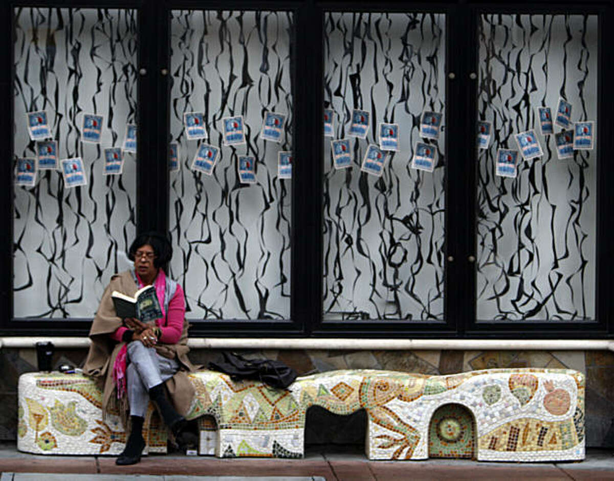 Angelina Toscano takes a break from office work to read a book on a custom painted artisan bench on Berkeley's Addison Street. Friday Jan 23, 2009