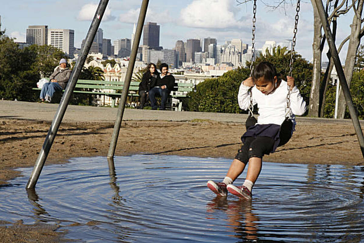 Aricelia Pablo watches the ripples underneath her as she plays on the flooded Dolores Park playground in San Francisco Calif, on Friday, Feb. 25, 2011.
