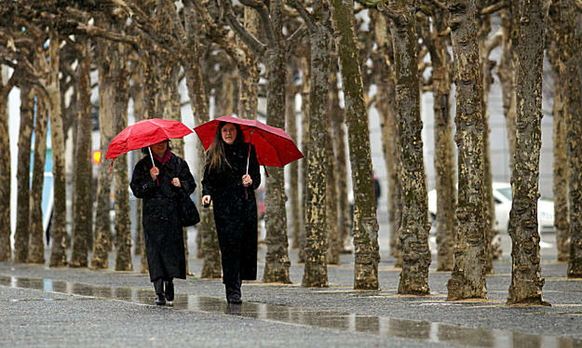Pearl Chan, (left) and Rosanne Torre, make their way through Civic Center Plaza, back to work at City Hall on Thursday Feb. 24, 2011, in San Francisco, Ca., as the next rain begins to move through the Bay Area bringing with it colder temperatures.
