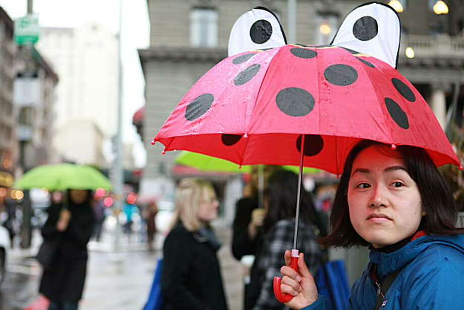 Asami Sugiuchi from LA uses her young daughters critter umbrella as she waits for her hotel shuttle in the rain at Union Square in San Francisco, Calif. on Thursday, February 24, 2011.   Kat Wade / Special to the Chronicle Photo: Kat Wade, Special To The Chronicle