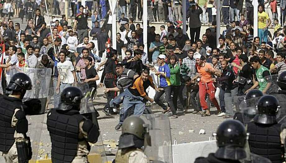 Iraqi riot police officers prevent anti-government protesters from entering the heavily guarded Green Zone during a demonstration in Baghdad, Iraq, Friday, Feb. 25, 2011. Thousands marched on government buildings and clashed with security forces in citiesacross Iraq on Friday, in the largest and most violent anti-government protests here since political unrest began spreading in the Arab world several weeks ago. Photo: Hadi Mizban, Associated Press