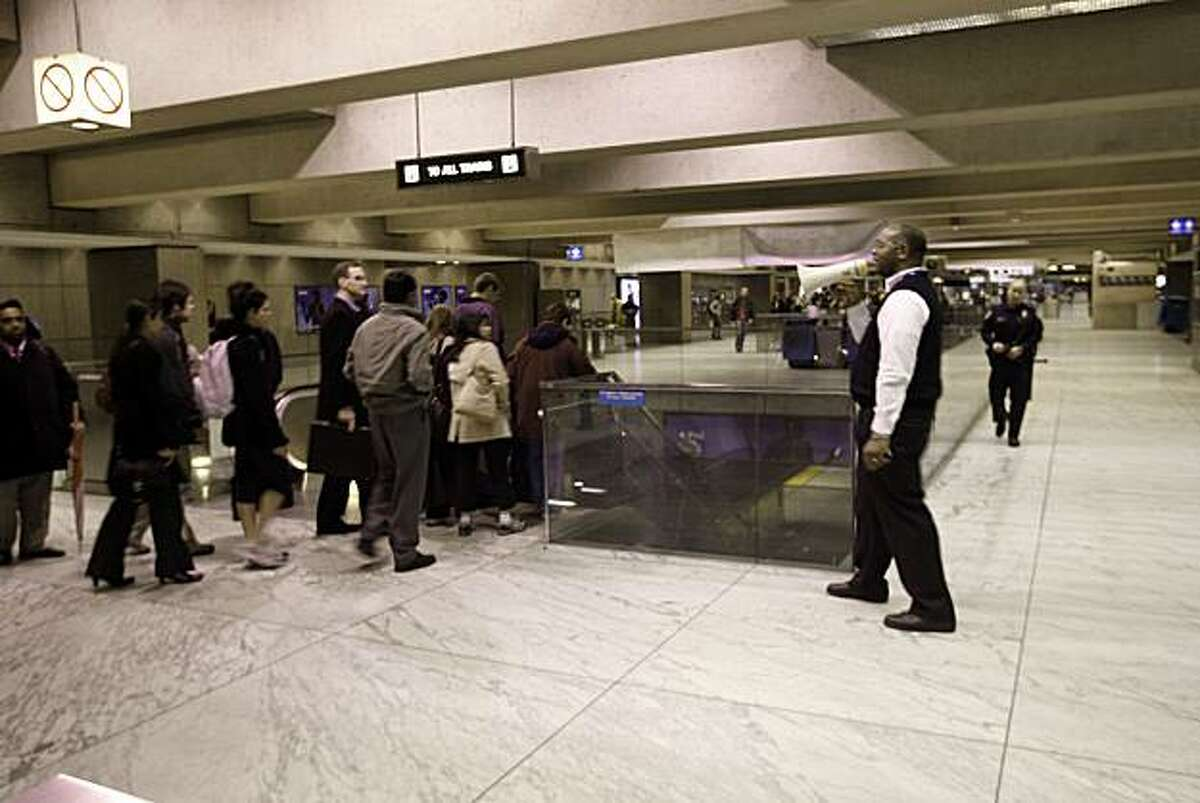 A BART employee herds riders back onto train platforms at the Embarcadero station.