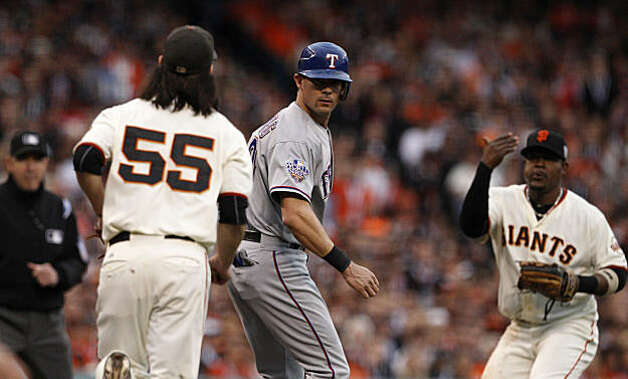 Giants Juan Uribe waits in vain for the throw from Tim Lincecum as they catch Rangers Michael Young in a run down.  Young was safe at third as the San Francisco Giants take on the Texas Rangers in Game 1 of the World Series at AT&T Park in San Francisco, Calif., on Wednesday, October 27, 2010. Photo: Carlos Avila Gonzalez, San Francisco Chronicle