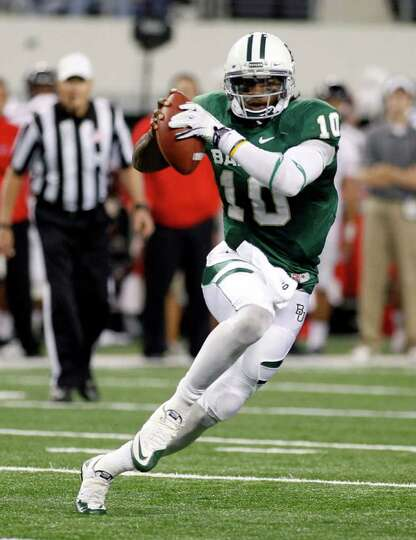 FILE - In this Nov. 26, 2011, file photo, Baylor quarterback Robert Griffin III scrambles during an