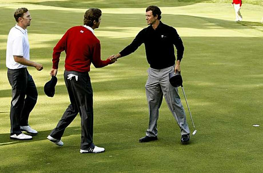 USA's Hunter Mahan, (left) and Sean O'Hair, (center) go down in defeat to Adam Scott, (right) and Ernie Els 2&1 on day one of the  2009 President's Cup Golf Tournament on Thursday October 8, 2009 at Harding Park golf course in San Francisco, Calif. prezcup09 Photo: Michael Macor, The Chronicle