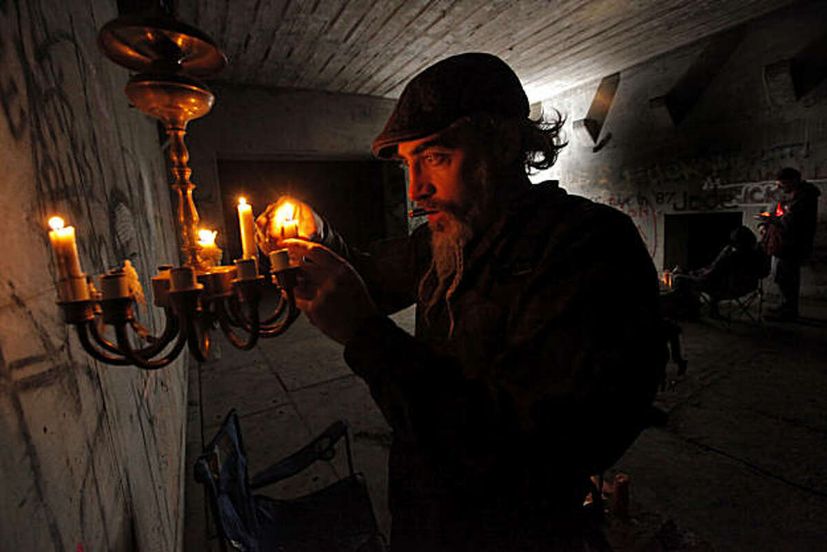 A young man who goes by the name of Louis Cypher lights candles in a candelabra that was left behind from other explores in the main cavity of an underground bunker, Sunday Feb. 13, 2011 in the Bay Area of Calif.