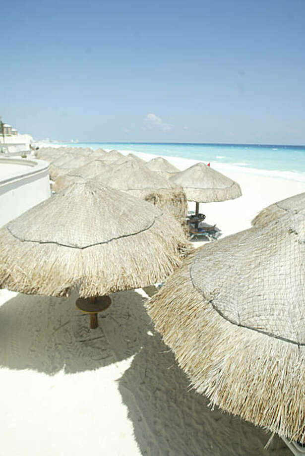 Palapas on the beach at the JW Marriott in Cancun, Mexico, which had it's official opening in September 2006, almost a year after Hurricane Wilma ravaged the island. Photo: Spud Hilton, The Chronicle