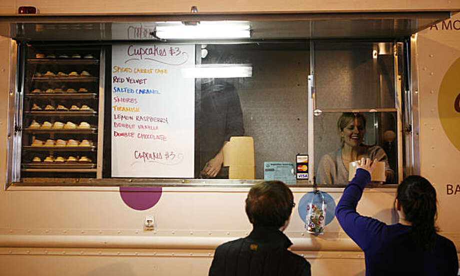 Kate McEachern, the owner of Cupkates, hands an order to a customer on Wednesday February 16, 2011. Off The Grid brings gourmet food trucks to the Minna Street alleyway every Wednesday. Photo: Anna Vignet, The Chronicle