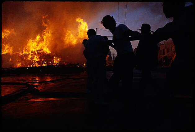 Civilians assist firefighters in extinguishing the massive block-long fire at Divisadero and Beach Streets in the Marina District, which was triggered by broken gas mains as result of the 1989 Loma Prieta earthquake.  This reader photo was taken facing north down Divisadero. Photo: Str8nochsr, Special To The Chronicle