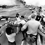 In this photo from October 17, 1989, Oakland Firefighters, California Highway Patrol, and others evacuate Erick Carlson from the Cypress section of Highway 17, now called Interstate 880, in Oakland, Calif., following the Loma Prieta Quake. (AP Photo/The Oakland Tribune, Michael Macor)